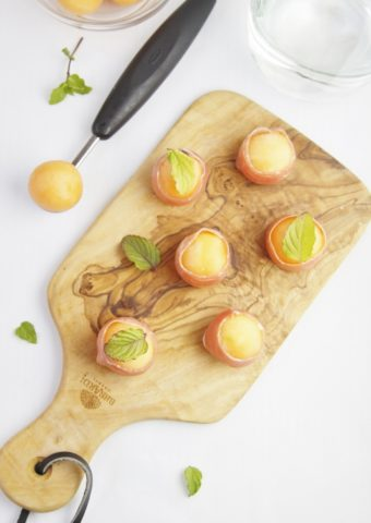 Prosciutto Wrapped Melon Balls on cutting board with melon scooper to side.