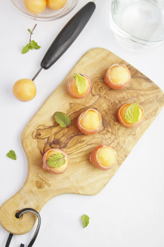 Prosciutto Wrapped Melon Balls on cuttinb board.