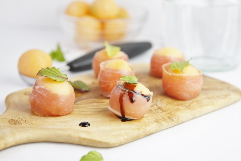 Prosciutto Wrapped Melon Balls on cutting board