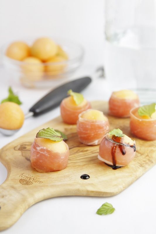 Prosciutto Wrapped Melon Balls on cutting board.