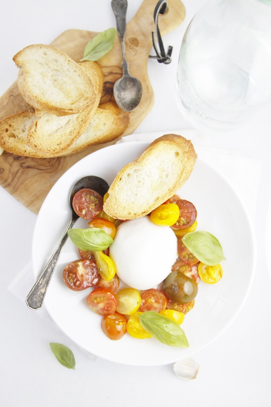 Burrata with Roasted Heirloom Tomatoes on white plate with slices of crostini bread on small wood cutting board in background.
