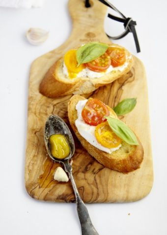 Burrata with Roasted Heirloom tomatoes crostini on small wood cutting board with spoon.