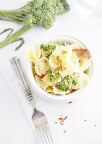 Cheesy Baked Pasta with Broccolini in white bowl. Fork and sprig of broccolini to side.
