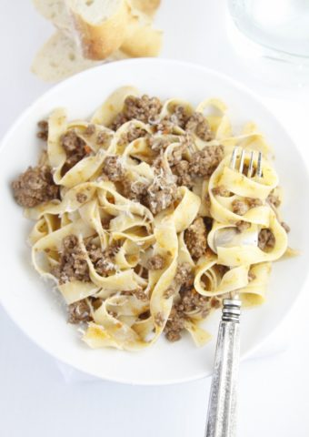 white bowl of pappardelle pasta with bolognese sauce