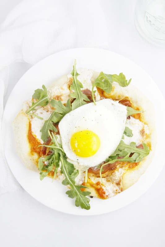 Prosciutto Arugula and Fried Egg Pizza on white plate with fork.