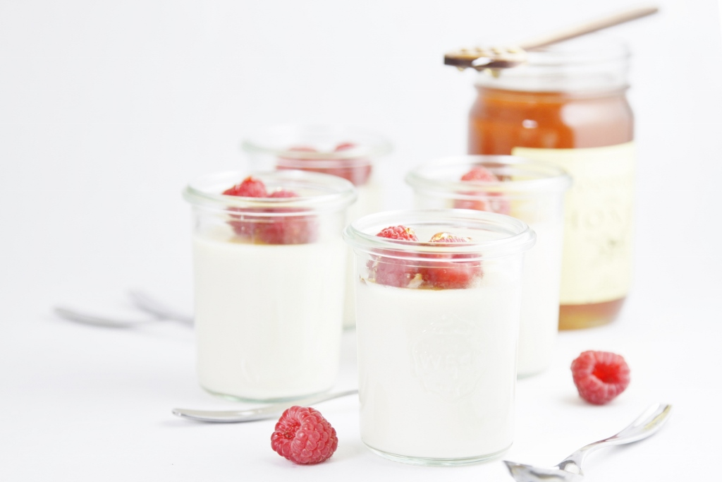 Chai Panna Cotta in small glass jars garnished with raspberries