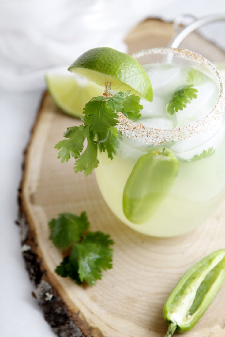 Cilantro Jalapeno Margaritas on wood platter with fresh cilantro and lime wedges scattered below.