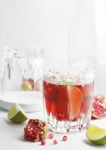 Pomegranate Lime Margarita with lime and pomegranates scattered around.