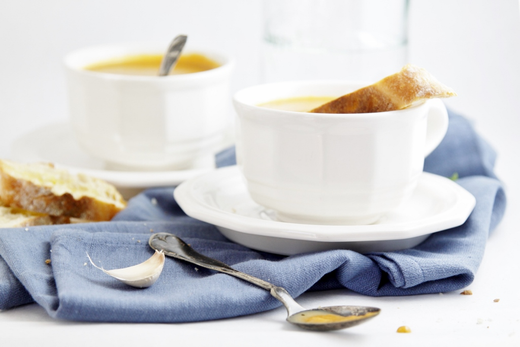 Creamy Roasted Pumpkin Soup in white cups with spoons.