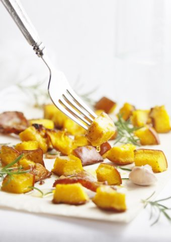 Roasted Pumpkin with Pancetta and Rosemary on a baking sheet with a fork piercing one piece