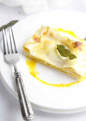 butternut squash lasagna on white plate with fork.