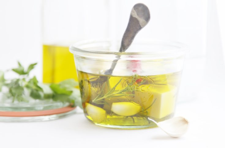 glass jar of marinated cheese cubes with spoon. Lid, fresh herbs and olive oil jar to side.
