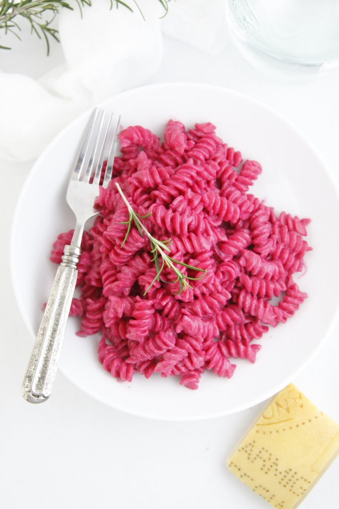 Pasta with Creamy Roasted Beet Sauce in white bowl with fork and wedge of parmiggiano cheese to side
