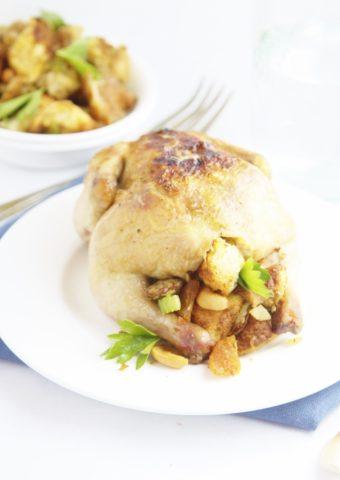 stuffed cornish hen on white plate.