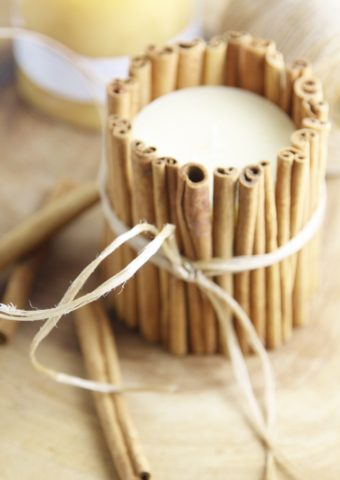 cinnamon sticks wrapped around a candle with kitchen twine.