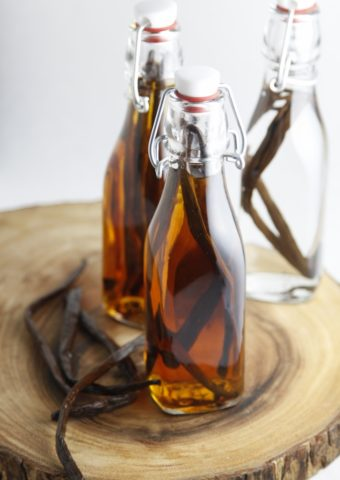 DIY Vanilla Extract in glass jars with vanilla beans to side