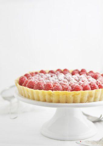 lemon tart with raspberries on white cake stand.