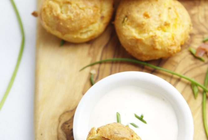 stack of Gougeres on cutting board with small white bowl of dipping sauce. Chives scattered around.