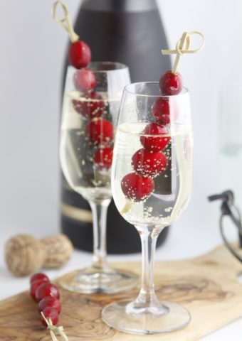 Two glasses of sparkling holiday cocktails. Wine bottle in background.
