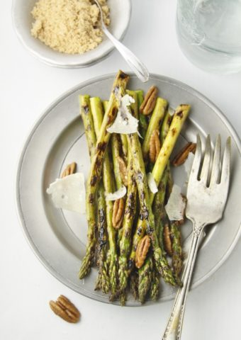 asparagus spears on metal plate with serving fork.