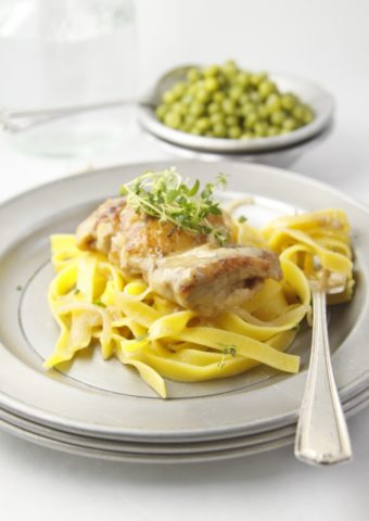 Slow Cooker Garlic Wine Chicken over pasta on metal plate.