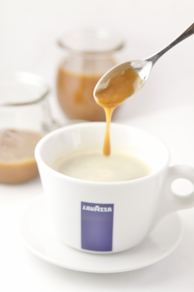 Spoon with Coffee Caramel Sauce dripping into cup of Lavazza coffee mug. Small glass jars of caramel sauce in background.