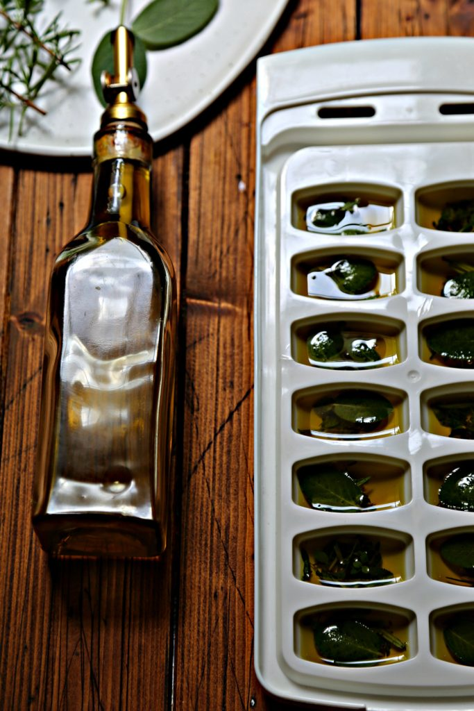 white ice cube tray filled with olive oil and herbs. Glass jar of olive oil on its side.