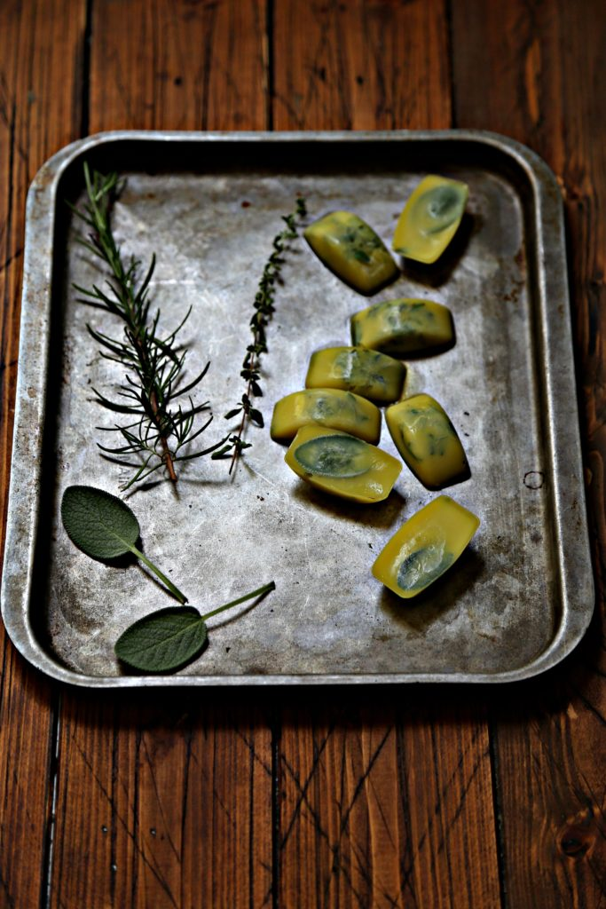preserved herb cubes on baking sheet with sprigs of fresh herbs.