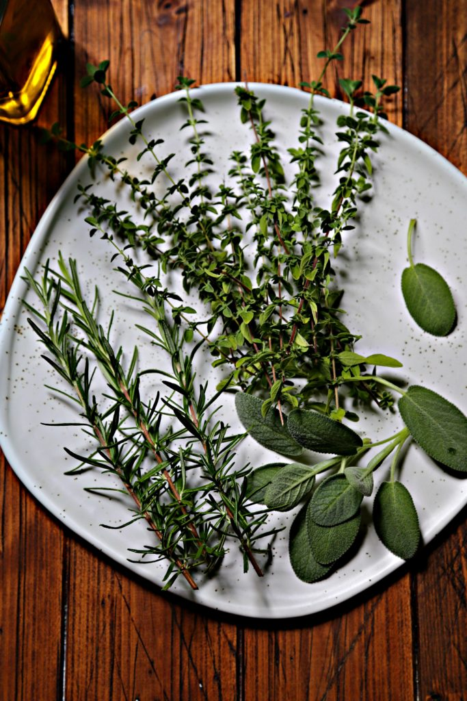 sprigs of fresh herbs on white plate. Glass jar of olive oil in background.