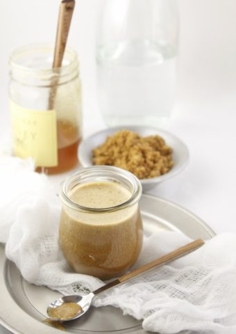 glass jar of brown sugar mustard glaze with spoon in front. Jar of honey and bowl of brown sugar behind.