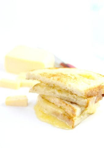 stack of grilled cheese sandwiches. cheese wedges and knife in background.