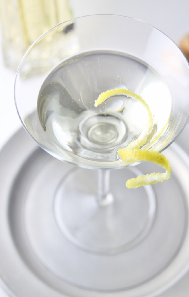 Top view of Hummingbird Cocktail in martini glass on a silver plate garnished with lemon peel.