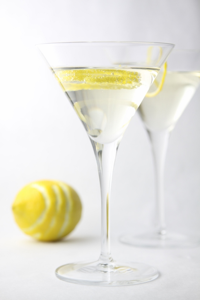 Two Hummingbird Cocktails in martini glasses garnished with lemon peel. Lemon missing peel to side.