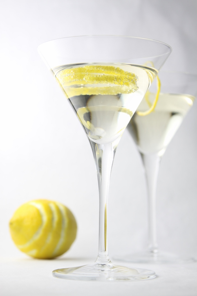 Two Hummingbird Cocktails in martini glasses garnished with a lemon peel. Lemon missing peel to side.