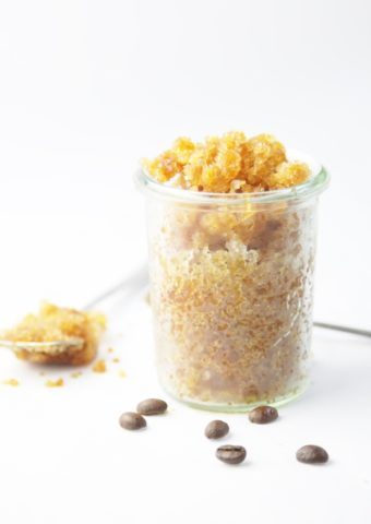 glass jar of coffee granita. Spoon full of granita and scattered coffee beans to side.