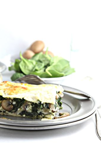 slice of spinach mushroom lasagna on silver plate with fork. Bowl of mushrooms and spinach behind.