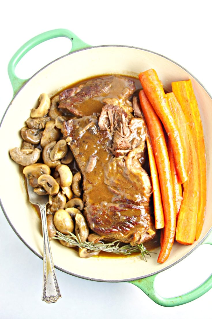 pot roast with mushrooms and carrots in a braising dish.