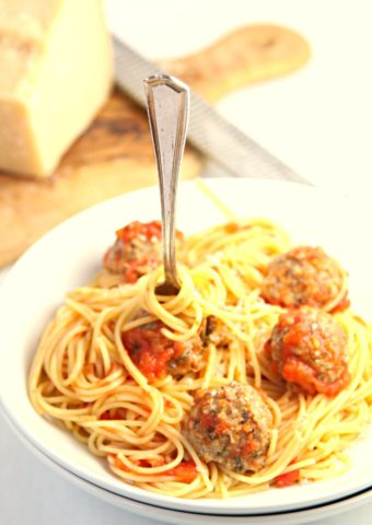Spaghetti and Meatballs in white bowl. Wedge of parm behind.