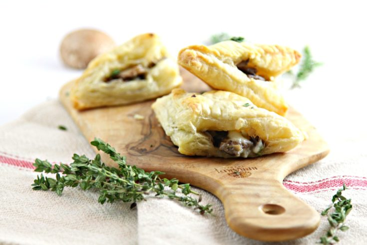 3 mushroom and brie puff pastry triangle appetizers on small cutting board. Sprigs of fresh time to side.