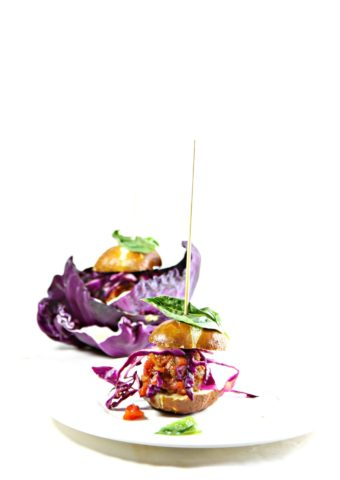 2 spicy meatball sliders on cutting board with skewers through top