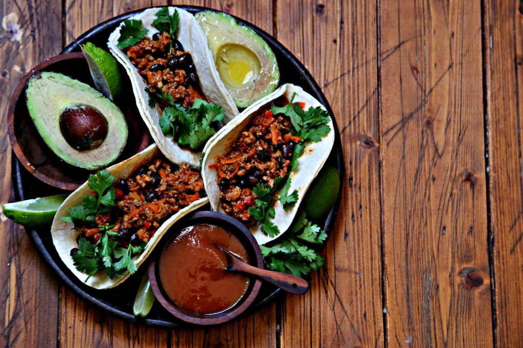 Black bean turkey tacos on brown plate with avocado and salsa.