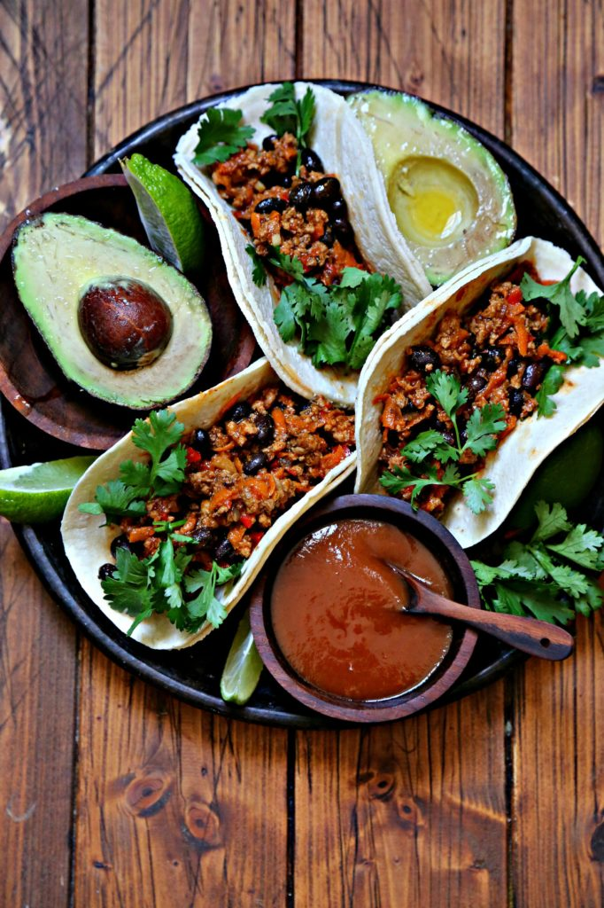 Black bean turkey tacos on brown plate with avocado and salsa