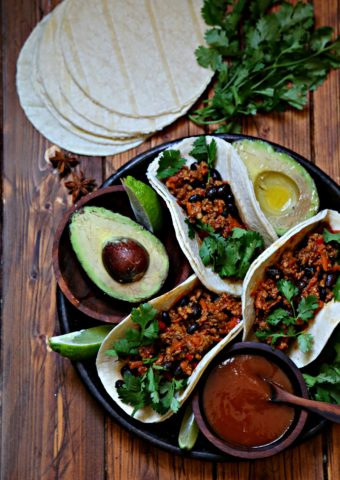 Black bean turkey tacos on brown plate with avocao and salsa. Tortillas behind.