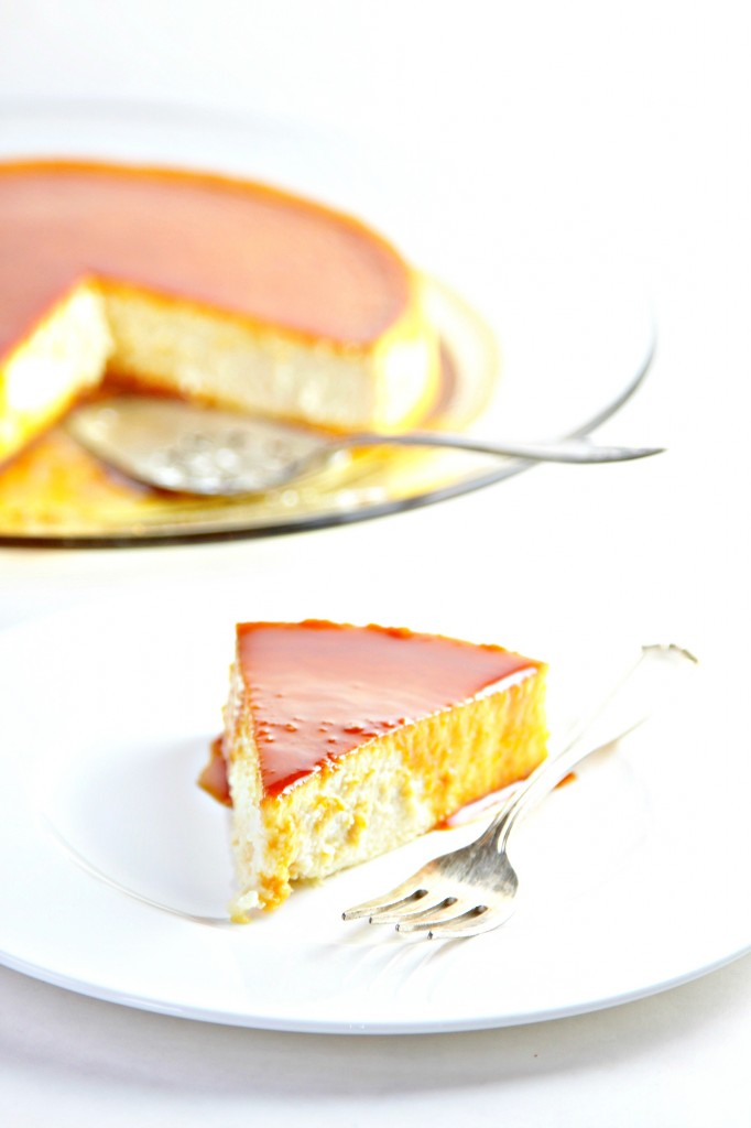 Cream Cheese Flan with Caramel Sauce on glass plate with serving utensil. Slice of flan on plate with fork in front.