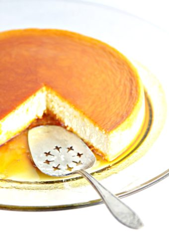 flan on glass plate with caramel sauce. Piece cut out and serving utensil in it's place.
