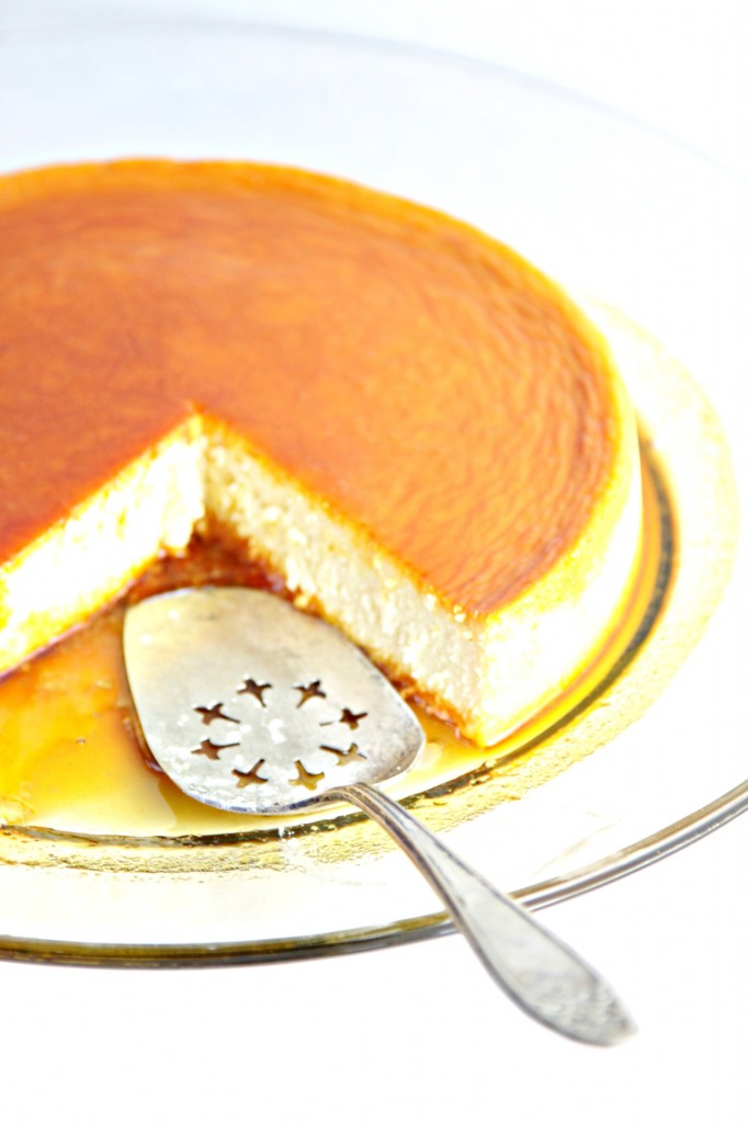 Cream Cheese Flan with Caramel Sauce on glass plate with serving utensil. Slice missing.