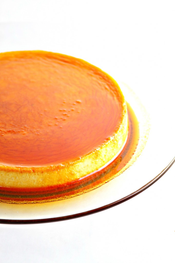 Cream Cheese Flan with Caramel Sauce on glass plate.