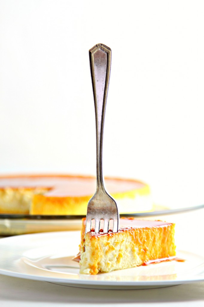 Slice of cream Cheese Flan with Caramel Sauce on plate with fork standing up in flan. Whole flan minus missing piece on glass plate in background.
