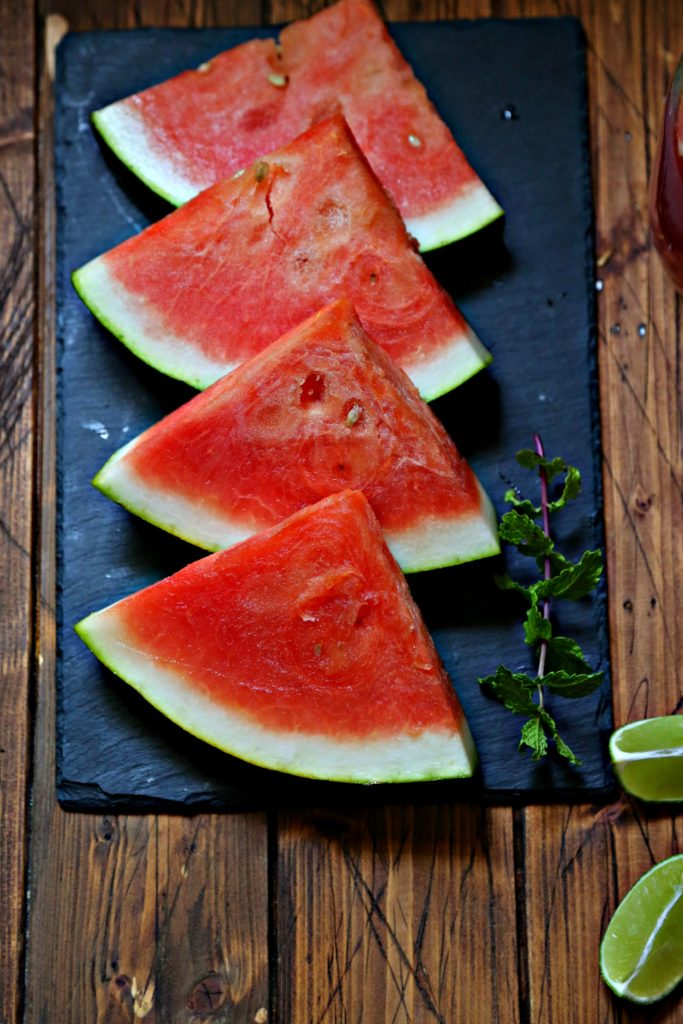 4 slices of watermelon laying on black slate. With fresh mint and lime wedges to side.