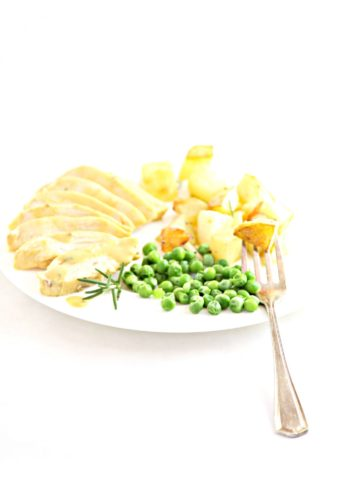 Maple Dijon Cicken sliced on white plate with fork and peas.
